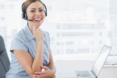 Auriculares vestindo de riso do agente do centro de chamada em sua mesa Fotografia de Stock