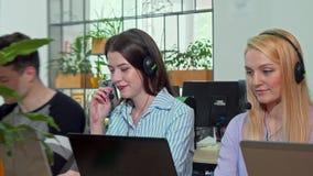 Auriculares vestindo do operador fêmea novo do apoio ao cliente, chamadas de resposta filme