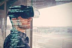 Auriculares vestindo do vr 3d do homem de negócios novo pela janela no escritório Imagens de Stock Royalty Free