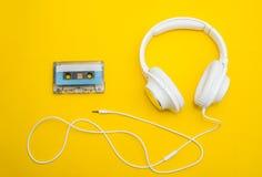 Auriculares y cinta blancos en amarillo fotos de archivo libres de regalías