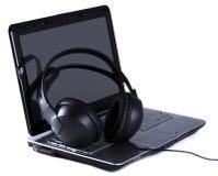 Auriculares y computadora portátil en el fondo blanco foto de archivo libre de regalías
