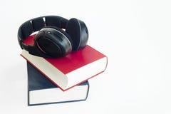 Auriculares y grupo de libros con el fondo aislado Imagenes de archivo