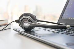 Auriculares y ordenador portátil del teléfono fotografía de archivo libre de regalías