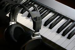 Auriculares y piano eléctrico Imagen de archivo