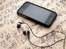 Auriculares y teléfono en fondo de la hoja de música Foto de archivo