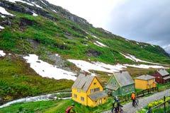 AURLAND, NORUEGA - JULIO DE 2015: Motoristas que caminan sus bicicletas a través de un pequeño carril al lado de la montaña verde Imagenes de archivo