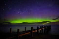 Aurora Australis show by the wharf. Urora Australis show by the wharf. Great green blue purple display of aurora with beams royalty free stock photos