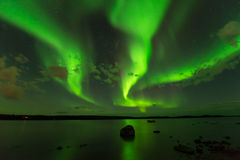 Aurora Beams. Three bright aurora beams scanning through the starry night sky over a lake stock photography