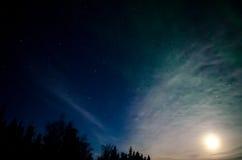 Aurora Behind the Moon. The moon shines through a faint green aurora Stock Photos