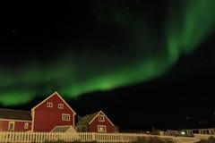 Aurora boreal e céu sobre duas casas vivas vermelhas, NU da luz das estrelas Fotografia de Stock Royalty Free