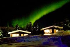 Aurora boreal sobre las cabañas de madera en la nieve Imagen de archivo