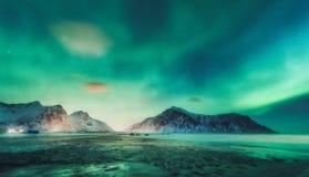 Aurora boreal sobre las rocas Cielo estrellado con las luces polares imagen de archivo