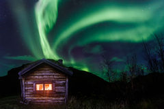 Aurora boreal sobre una choza vieja Foto de archivo