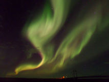 Aurora boreal verde e cor-de-rosa excitante da cor que dança sobre a ponte, Islândia foto de stock