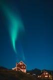Aurora boreal verde que aumenta como o fumo da casa vermelha na noite em Gronelândia fotos de stock