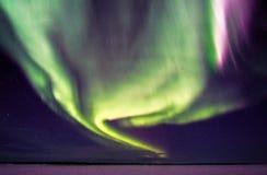 Aurora boreal y estrellas que remolinan sobre el lago congelado Fotografía de archivo