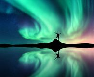 Aurora boreal y hombre cerca del lago con la reflexión en agua imagen de archivo