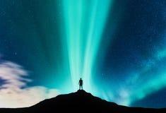 Aurora boreale e siluetta dell'uomo diritto sulla montagna fotografie stock