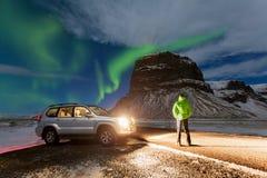 Aurora borealis über dem Mann und dem Auto in Island Grüne Nordleuchten Sternenklarer Himmel mit Polarlichtern stockbilder