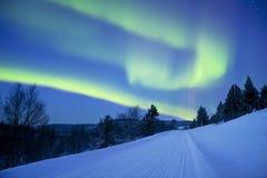 Aurora borealis über einer Straße durch Winterlandschaft, finnisches La Stockbilder