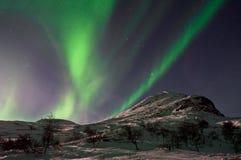 Aurora Borealis above mountain hill. Captured near Skibon, Norway stock photography