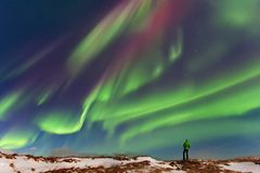 Aurora borealis above the silhouette maa in Iceland. Green northern lights. Starry sky with polar lights. stock photos