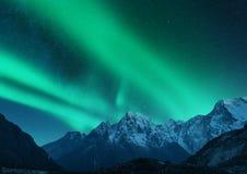 Aurora borealis above snow covered mountain range in europe. Aurora borealis above the snow covered mountain range in europe. Northern lights in winter. Night royalty free stock image