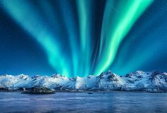 Aurora borealis above the snow covered mountains stock images