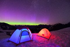 Aurora Borealis And Tents On Snow Mountain Royalty Free Stock Photos
