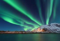 Aurora borealis boven de sneeuw behandelde berg stock afbeelding