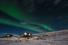 Aurora Borealis with cottage houses in winter Royalty Free Stock Image