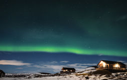 Aurora Borealis with cottage houses in winter Stock Photos