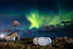 Aurora borealis da aurora boreal sobre a casa da exploração agrícola na cidade de Gardur imagem de stock