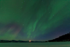Aurora borealis dance moonrise Lake Laberge Yukon Stock Image
