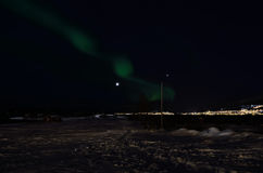 Aurora borealis dancing over snowy field near sea shore. With full moon Stock Photos