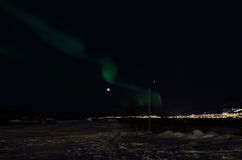 Aurora borealis dancing over snowy field near sea shore with full moon. Background Royalty Free Stock Image