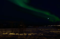 Aurora borealis dancing over snowy field near sea shore. With full moon Royalty Free Stock Photography