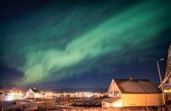 Aurora borealis die over Skandinavisch dorp dansen stock foto