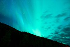 The Aurora Borealis emerges through clouds remote Alaska. The Northern Lights appear in remote country also called the Aurora Borealis royalty free stock photos