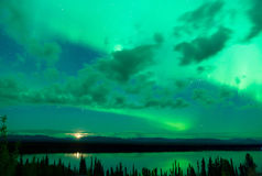The Aurora Borealis emerges through clouds remote Alaska Stock Image
