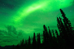 The Aurora Borealis emerges through clouds remote Alaska Stock Photography