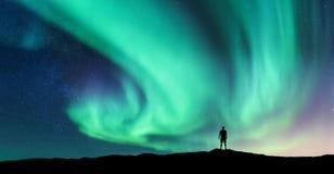 Aurora borealis en silhouet van de bevindende mens stock fotografie