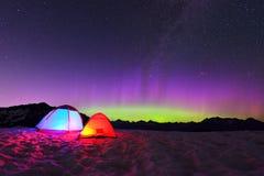 Aurora borealis en tenten op sneeuwberg royalty-vrije stock afbeelding