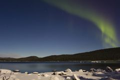 Aurora Borealis in finnish Lapland. Aurora Borealis / Northern or Polar light with green light at full moon - Inari lake - finland - Lapland - Scandinavia Royalty Free Stock Image