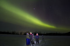 Aurora Borealis in finnish Lapland. Photographers watching and taking Pictures of the Aurora Borealis with green and purple light at Inari lake, finland, Lapland Royalty Free Stock Photo
