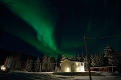 Aurora borealis forte sobre a casa e a floresta imagens de stock royalty free