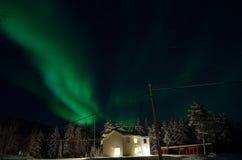 Aurora borealis forte sobre a casa e a floresta imagem de stock royalty free