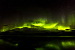Aurora Borealis Green Over Lake. Green aurora borealis or northern lights in the night sky over a reflective lake Stock Image