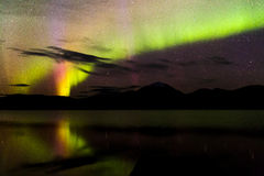 Aurora Borealis Green and Purple Over Lake. Green and purple aurora borealis or northern lights in the night sky over a reflective lake Stock Images
