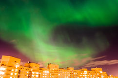Aurora borealis groene sterrige nacht over de stad en de huizen stock fotografie